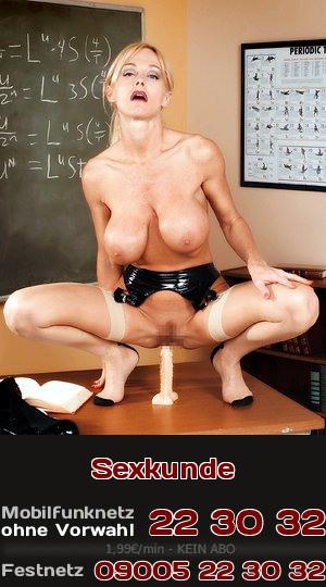 Fantasie für Telefonsex: Eine Lehrerin, halb nackt in Dessous, führt sich auf dem Lehrerpult leidenschaftlich einen Dildo ein.