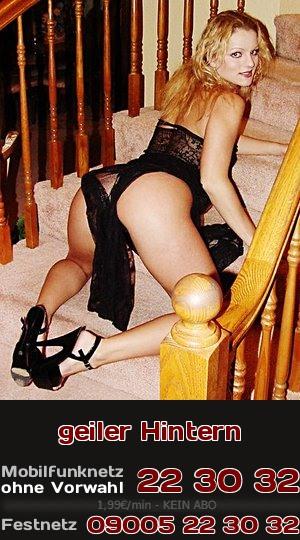 Eine Telefonsex-Blondine präsentiert ihren geilen Hintern auf den Stufen einer Treppe.